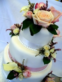 Three tier wedding cake, fondant covered, fresh pastel roses and lilies by Goodies Bakeshop