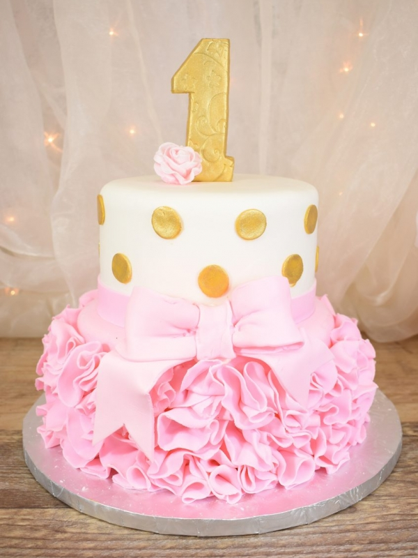 Two Tier First Birthday Cake by Goodies Bakeshop with Gold Fondant, Pink Ruffles and Bow