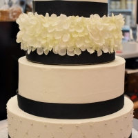 Wedding Cake by Goodies Bakeshop four tier with silk flowers and black ribbon